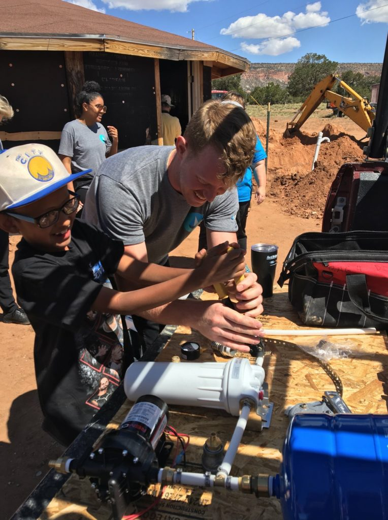 George McGraw, founder of DigDeep and the Navajo Water Project, works on a sink installation with a young member of the Navajo community