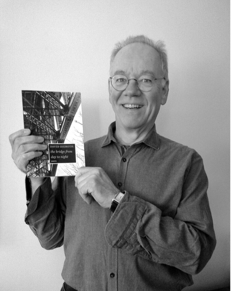 David Zieroth holding up his latest collection of poems, the bridge from day to night.